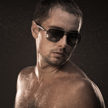 Attractive young man covered with water drops photo