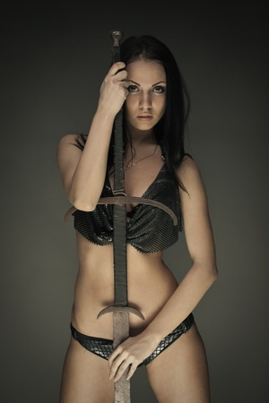Portrait of gorgeous brunette woman with long rusty sword photo