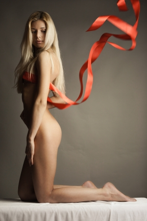bare breasts: Portrait of naked woman wearing red ribbon as lingerie