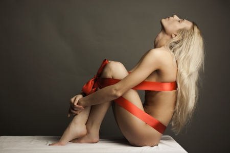 nude back: Portrait of naked woman wearing red ribbon as lingerie. Body packaged as present with bow Stock Photo