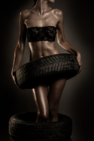 Young fit woman holding tire of car photo