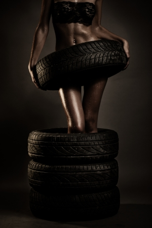 Young fit woman holding tire of car Archivio Fotografico