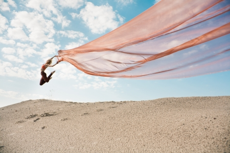 Girl dancing with long orange transparent cloth