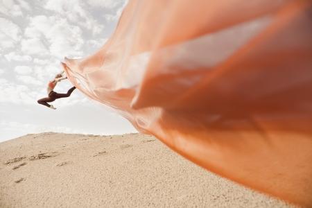 salto largo: Baile de la muchacha con el pa�o transparente anaranjado largo