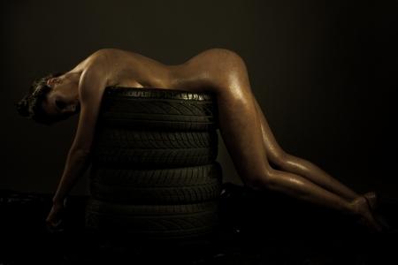 chica desnuda: Beatiful curvas del cuerpo femenino tumbado en neum�ticos