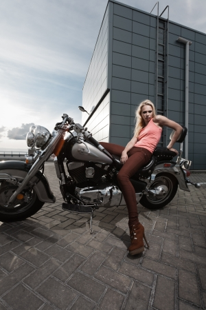 Fashion portrait of young attractive blond girl on motorcycle photo