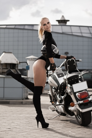 Fashion portrait of young attractive blond girl and motorcycle photo