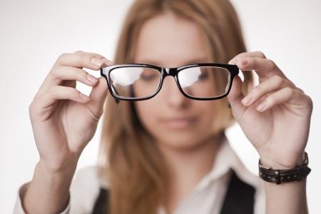 Girl holding glasses, selective focus on glasses  Concept  poor eyesight