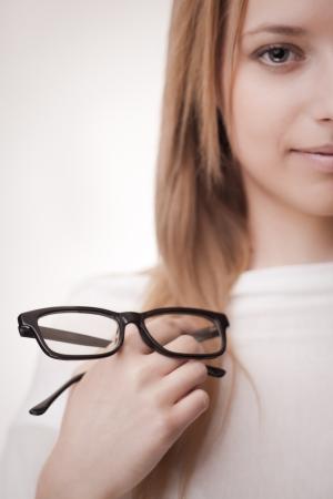 poor eyesight: Girl holding glasses, selective focus on glasses  Concept  poor eyesight
