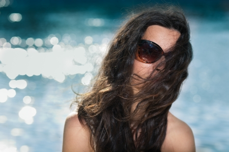 Portrait of young brunette girl in sunglasses on beach  Copy space on left photo