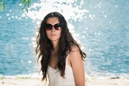 Portrait of young brunette girl in sunglasses on beach photo