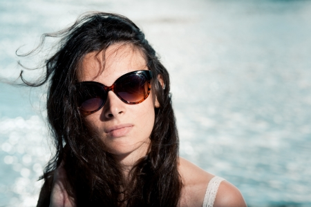 Portrait of young brunette girl in sunglasses on beach  Copy space on right photo