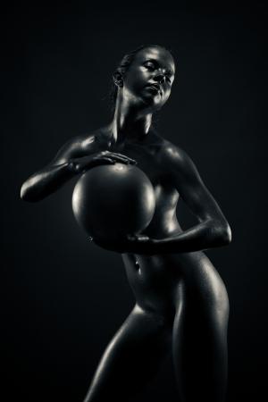 Metallic woman holding ball, isolated on black background