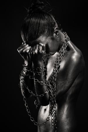 corps femme nue: Concept de la limitation de la liberté: femme d'argent nue avec les mains dans les chaînes