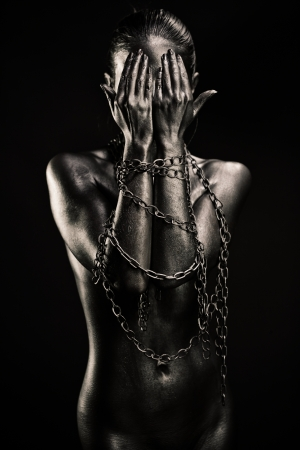 naked statue: Concept of freedom limitation: nude silver woman with hands in chains closing her face