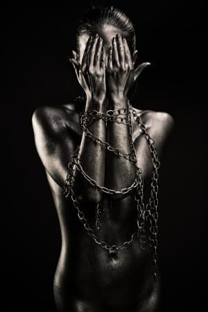 mujeres negras desnudas: Concepto de la limitación de la libertad: la mujer desnuda de plata con las manos en las cadenas de cierre de la cara