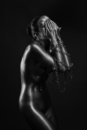 mujeres negras desnudas: Concepto de limitaci�n de la libertad: la mujer desnuda de plata con las manos en las cadenas Foto de archivo