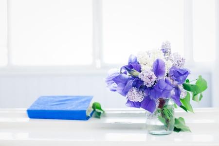 Simple still life - book and bouquet on window Archivio Fotografico