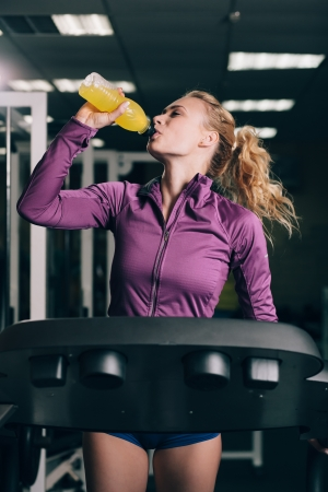 Young blond woman  jogging and drinking in gym