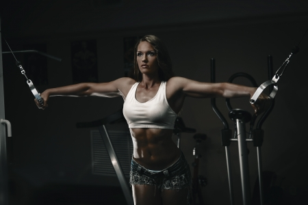 Brunette woman doing chest expand on gym machine