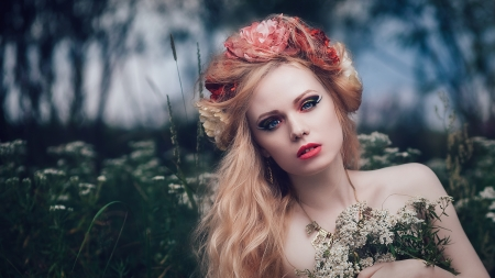 Art fashion portrait of young blond girl with flowers in hair on meadow photo