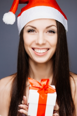 Gorgeous cheerful santa girl on gray photo