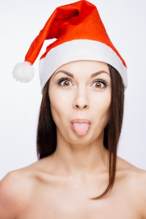 Gorgeous crazy funny santa girl showing tongue, isolated on white photo