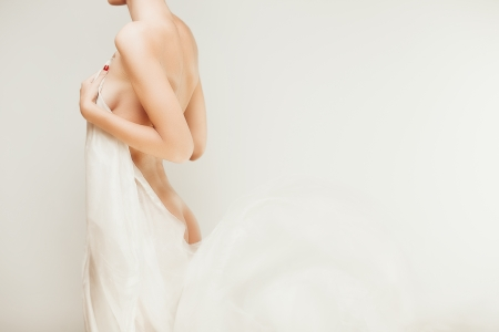 Beautiful naked body of young woman with transparent cloth over white background