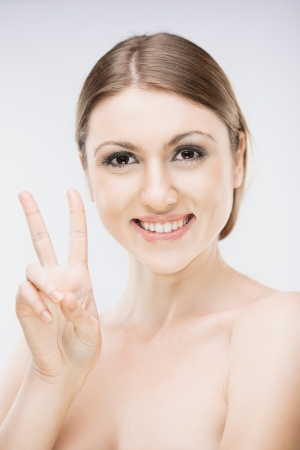 Fashion artistic portrait of brunette girl showing hand sign of peace photo