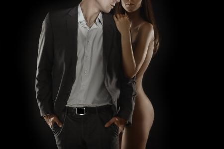 Artistic portrait of young elegant couple on black