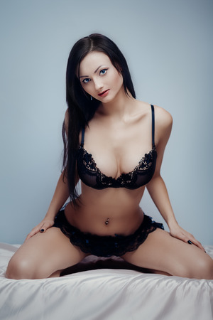 Fashion portrait of young sexy brunette on bed photo