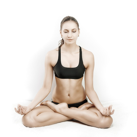 Young woman sitting in lotus pose photo