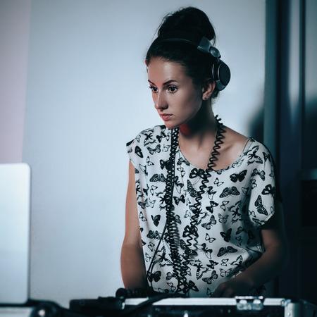 Female dj at work in night club. Shallow depth of field photo