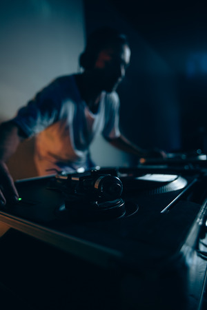 Male dj at work in night club. Selective focus on foreground photo