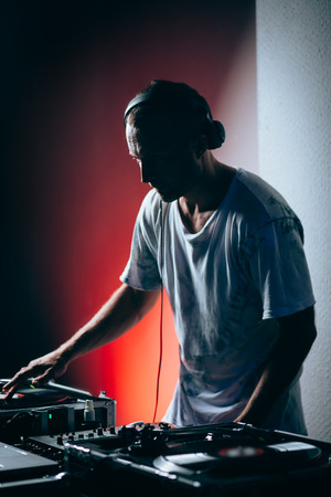 Silhouette of dj at work in night club. Shallow depth of field photo