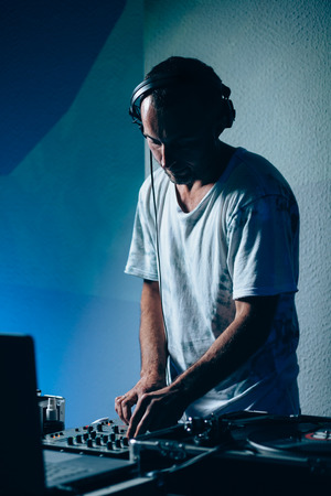 Male dj at work in night club. Shallow depth of field photo