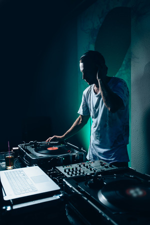 Silhouette of dj at work in night club. Shallow depth of field Banque d'images