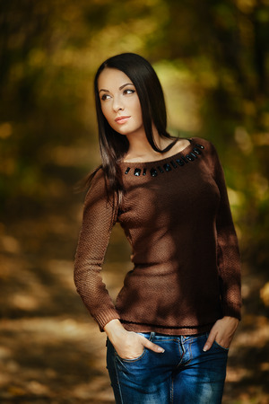 Art fashion portrait of young gorgeous brunette in the fall. Shallow depth of field photo