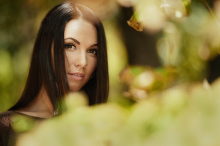 Art fashion portrait of young brunette through leaves. Shallow depth of field photo