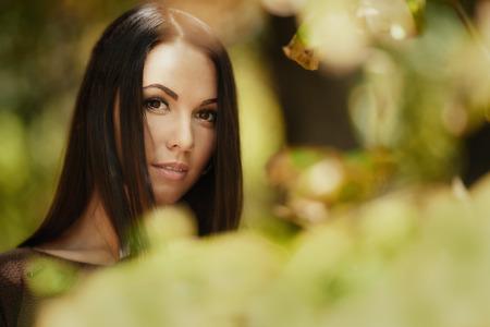 belle brunette: Art portrait de la mode jeune femme brune à travers les feuilles. Faible profondeur de champ Banque d'images