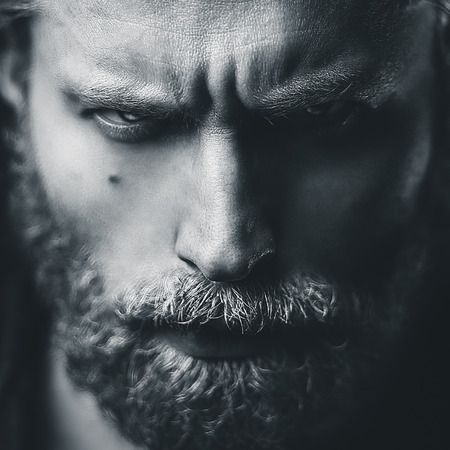 Artistic portrait of angry mid aged man with white hair and beard. Shallow depth of field Stock Photo
