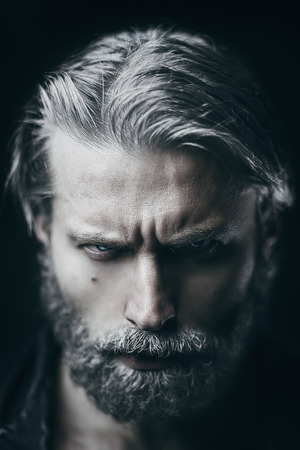 white men: Artistic portrait of angry mid aged man with white hair and beard. Shallow depth of field Stock Photo