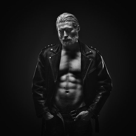 Artistic portrait of muscular mid aged handsome man with gray hair