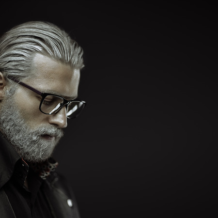 Artistic portrait of gray haired man on black background