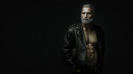 gray haired: Artistic portrait of gray haired man on black background