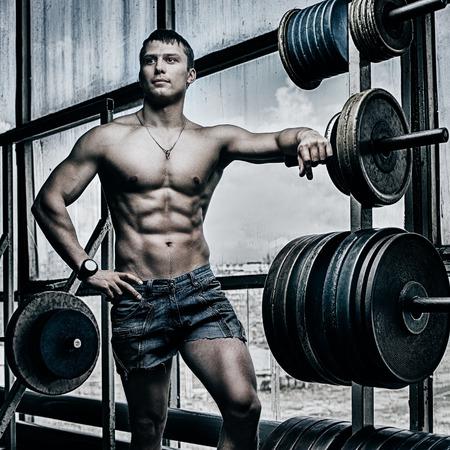 sin camisa: Atleta hermoso joven en el gimnasio viejo oxidado