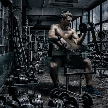 rusty: Atleta hermoso joven en el gimnasio viejo oxidado
