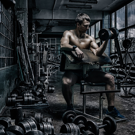 Young handsome athlete in old rusty gym photo