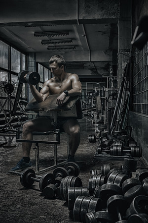 hard: Young handsome athlete in old rusty gym