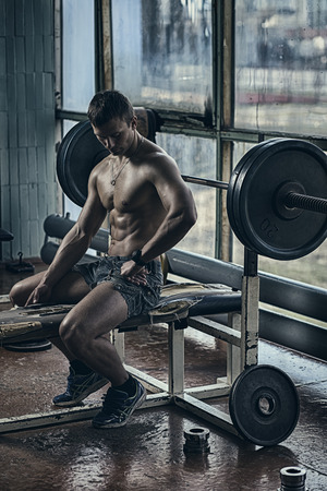 Young handsome athlete in old rusty gym